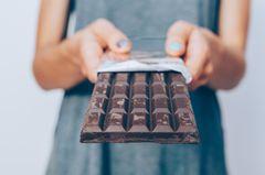 Schokolade gegen Husten: Frau hält Schokoladentafel