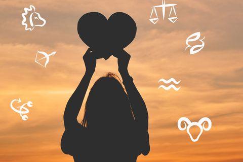 Welches Sternzeichen passt zu Wassermann: Eine Frau bei Sonnenuntergang hält ein Herz hoch