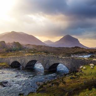 Coorie: Gemütlichkeit auf schottisch: Berge in Schottland, davor ein Fluss mit einer Steinbrücke