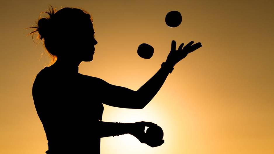 Jonglieren lernen: Frau jongliert vorm Sonnenuntergang