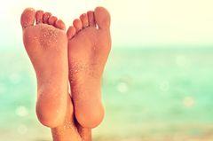 Fußpeeling: Zwei Füße am Meer mit Sand auf der Fußsohle