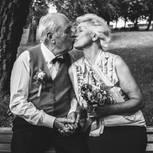 Diamantene Hochzeit: Gedichte und Geschenkideen zum Jubiläum: Senioren-Ehepaar sitzt auf einer Parkbank und küsst sich