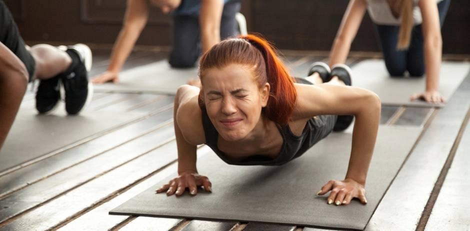 Drunk Yoga: Frau beim Yoga mit angestrengtem Gesicht