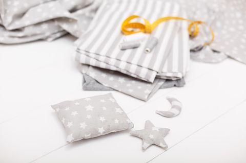 Körnerkissen nähen in 6 einfachen Schritten: Kleines Kissen auf dem Tisch, dahinter Stoffmuster und Garn