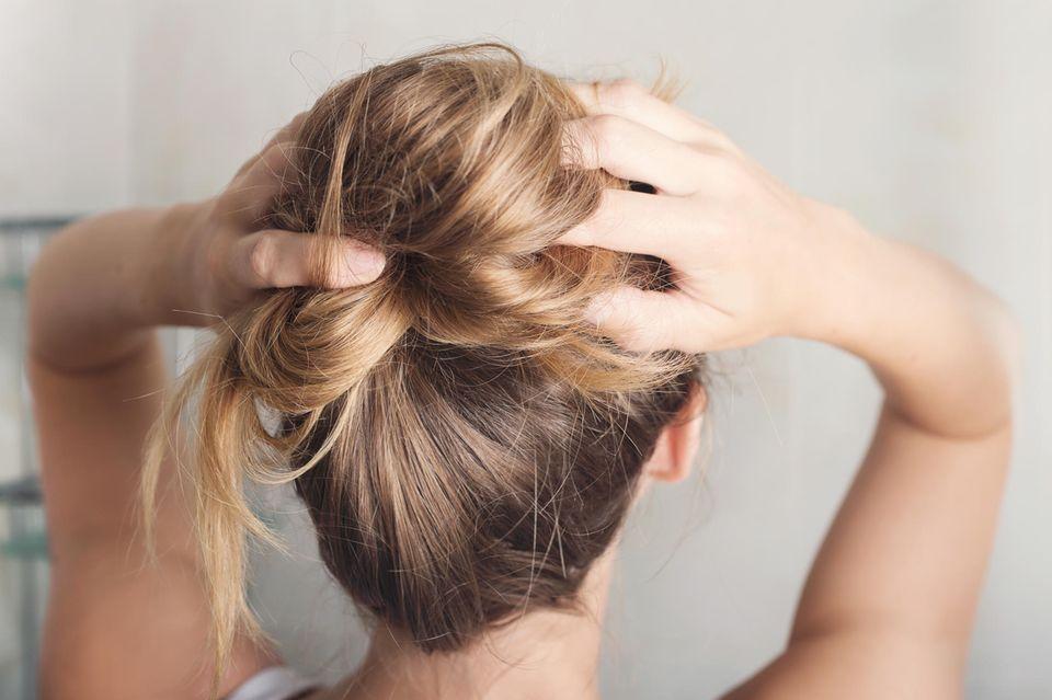 Wir haben Trockenshampoo jahrelang falsch benutzt: Frau, die sich in die Haare fässt