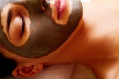 Poren reinigen: Frau mit Maske aus Heilerde im Gesicht