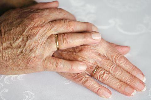 Eiserne Hochzeit: Bedeutung, Geschenkideen und Sprüche: Hände eines älteren Ehepaares liegen übereinander