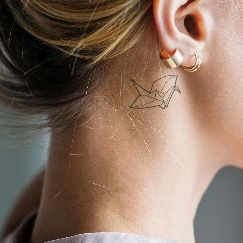 Tattoo Motive: Eine Frau mit einem zarten Origami-Schwan hinterm Ohr