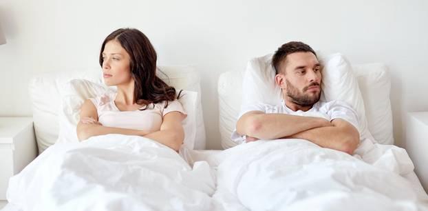 Das Hauptproblem in Beziehungen: Ein Paar liegt beleidigt und voneinander abgewandt im Bett
