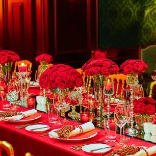 Rubinhochzeit: Bedeutung, Deko und Geschenkideen: Feierlich gedeckte Tafel in rot mit roten Blumensträußen