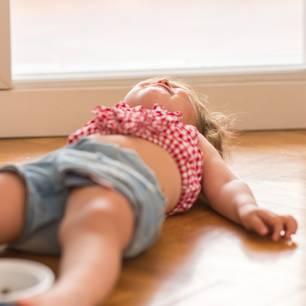 Kleinkind liegt auf dem Boden