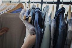 Zeitfresser loswerden: Eine Frau nimmt sich Klamotten von der Kleiderstange