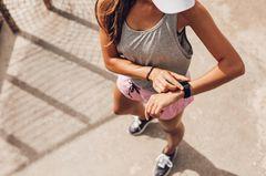 Zeitfresser loswerden: Eine Frau in Sportklamotten checkt ihre Apple Watch