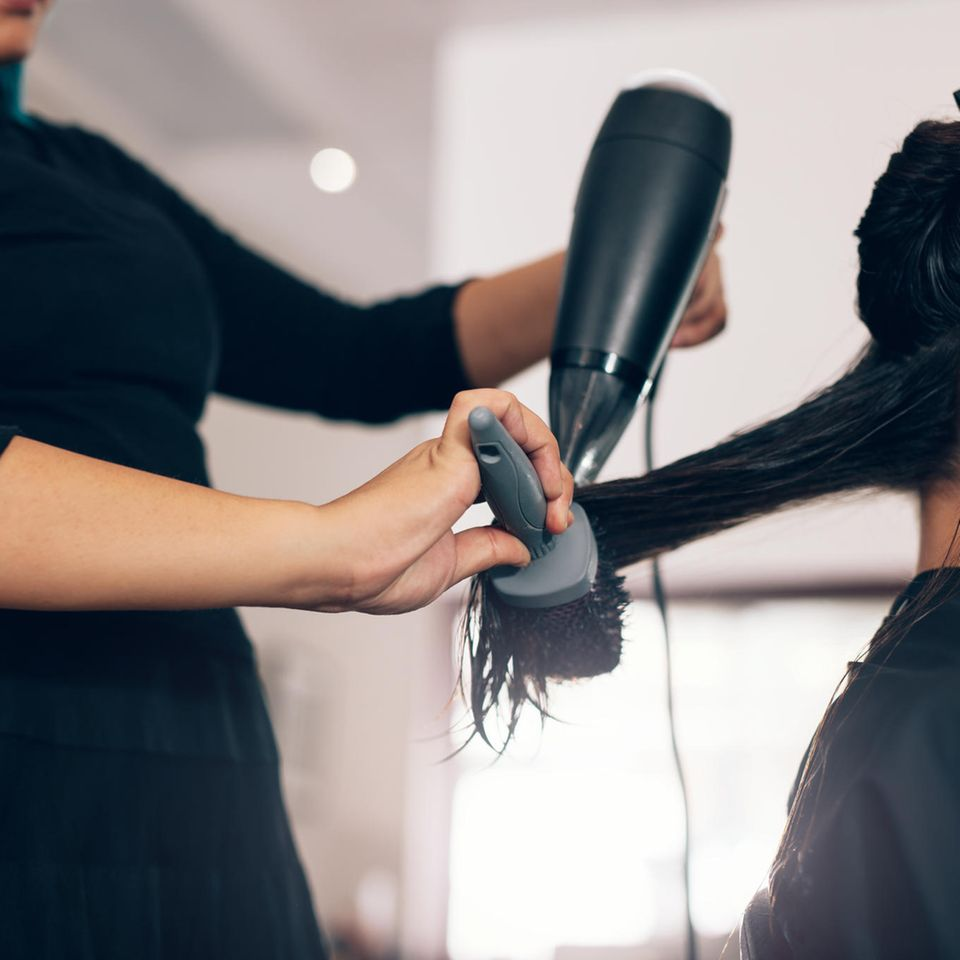 Friseur Gehalt: Friseur kämmt und föhnt Haare einer Frau