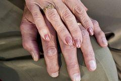 Goldene Hochzeit: Eine alte Frauenhand mit Ehering auf einer Männerhand