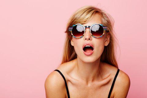 G-Punkt aufspritzen: Frau guckt lasziv in Kamera mit Sonnenbrille