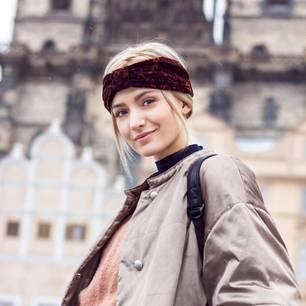 Haarband nähen: 2 Varianten ohne Schnittmuster: Frau mit dunkelrotem Haarband steht vor einem historischen Gebäude