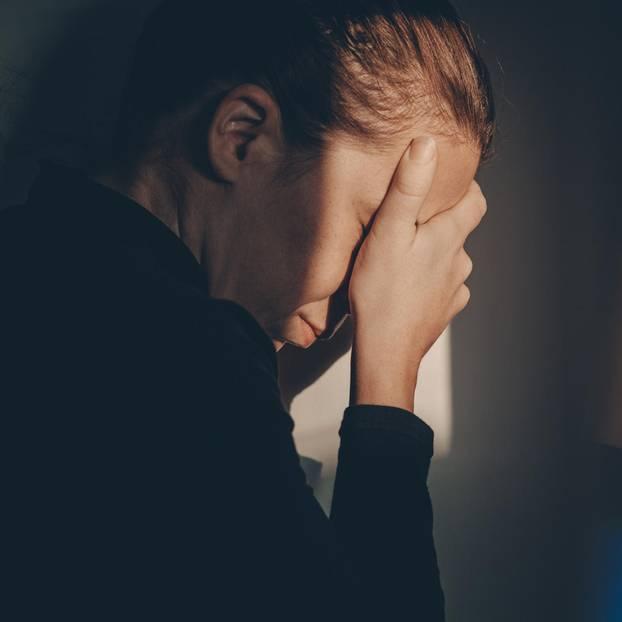 Schuldgefühle nach Abtreibung: Frau vergräbt Gesicht in der Hand