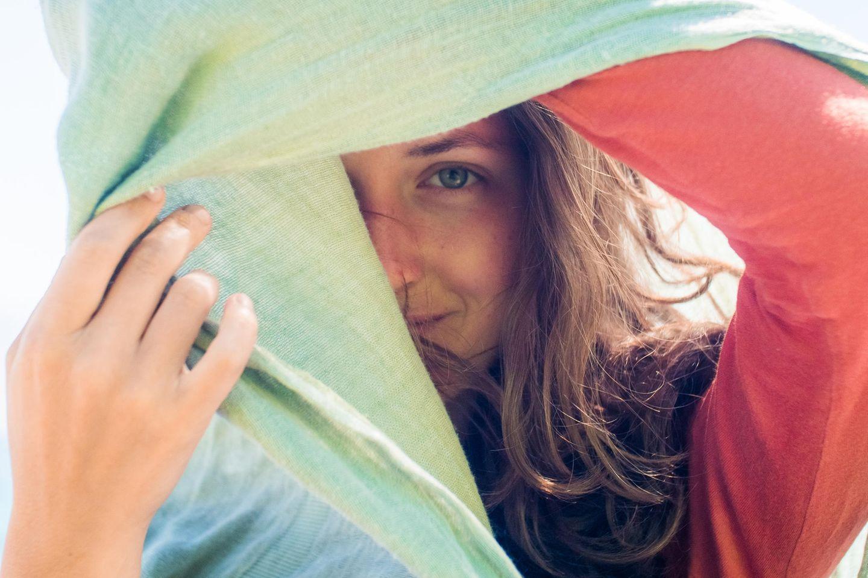 Wann sind Selbstzweifel gut? Eine Frau versteckt sich halb hinter einem Tuch