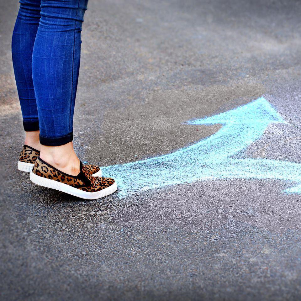 Entscheidungen treffen: Frau steht an aufgemalter Kreuzung