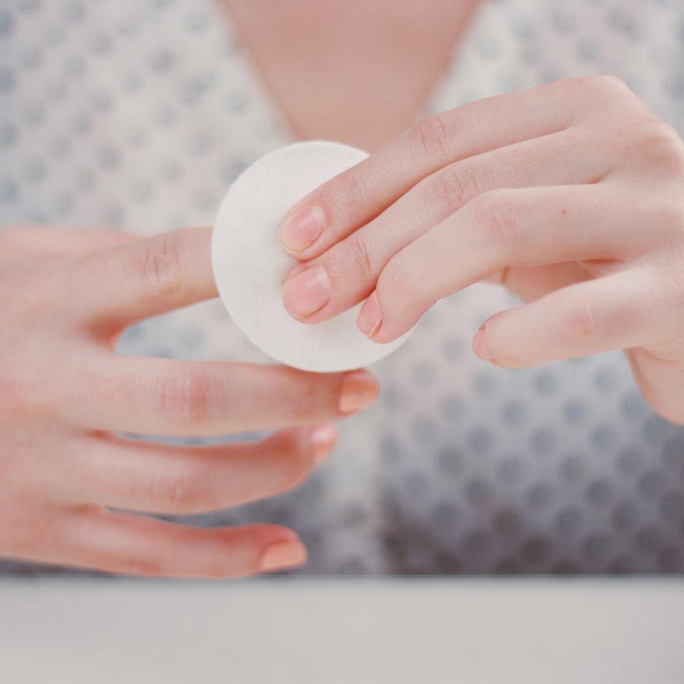 Acrylnägel entfernen: Zwei Hände, die mit Wattepad Nagellack entfernen