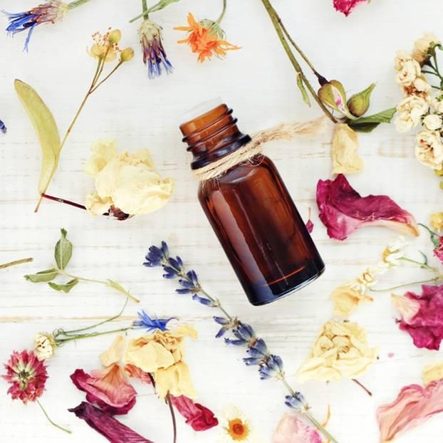 Massageöl selber machen: schnell und unkompliziert: Viele getrocknete Blüten und eine kleine dunkle Flasche