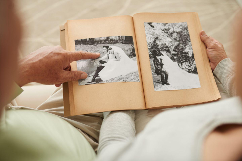 Gnadenhochzeit: Bedeutung, Geschenke und Glückwünsche: Älteres Pärchen blättert in einem alten Fotoalbum mit Hochzeitsbildern