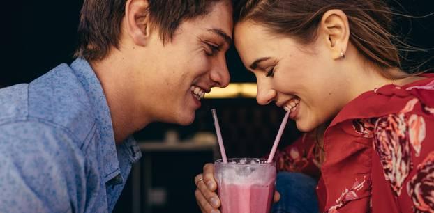 Erstes Date: Ein junges Pärchen teilt sich einen rosa Milchshake