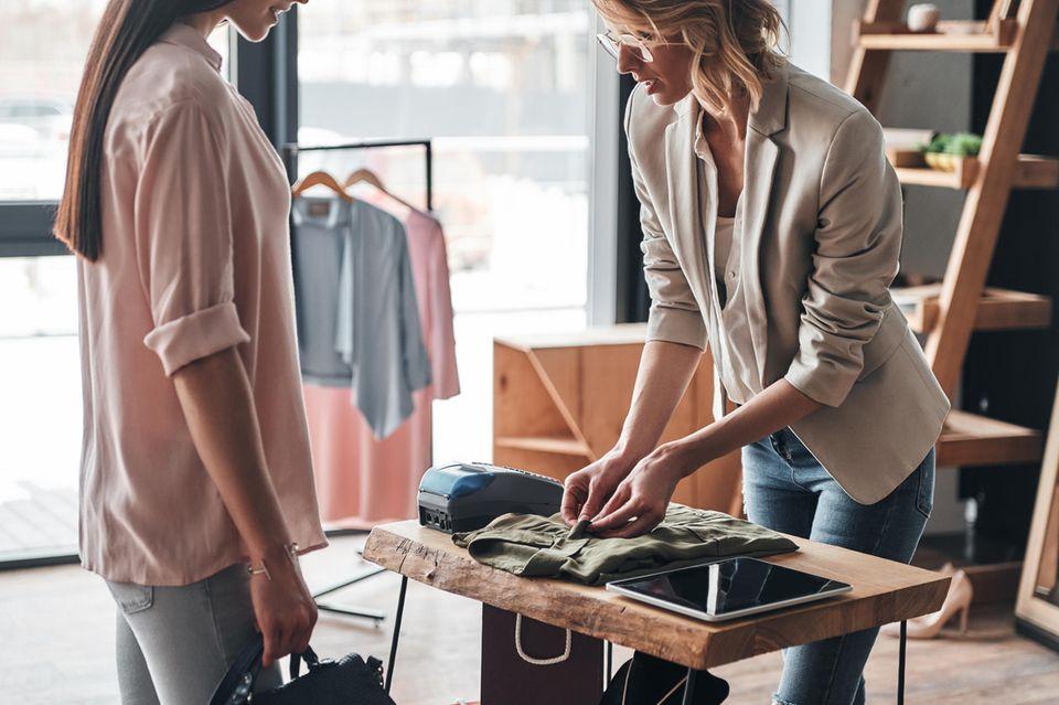 Einzelhandelskauffrau Gehalt: Verkäuferin in Modegeschäft kümmert sich um Kundin