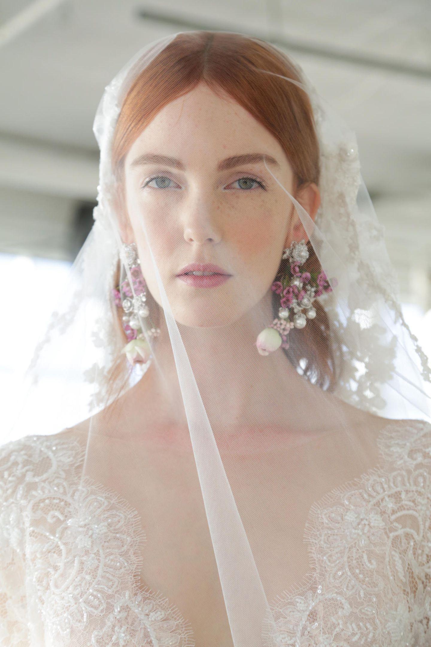 Brautfrisur mit Schleier: Braut mit Schleier und Ohrringen