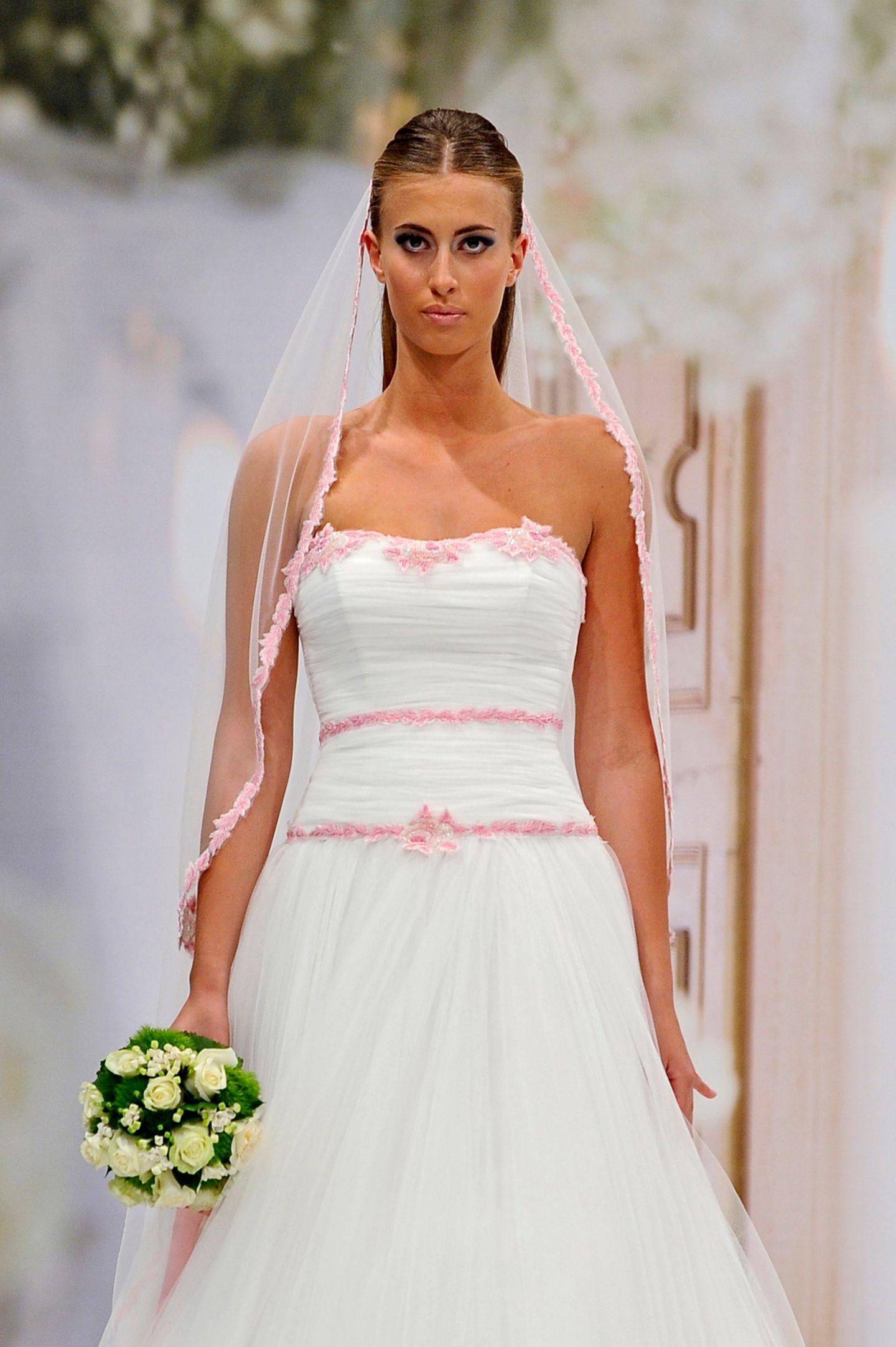 Brautfrisur mit Schleier: Frau mit Brautkleid, zweifarbigem Schleier und Brautstrauß