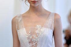 Brautfrisuren: Frau in Brautkleid und lockerer Hochsteckfrisur