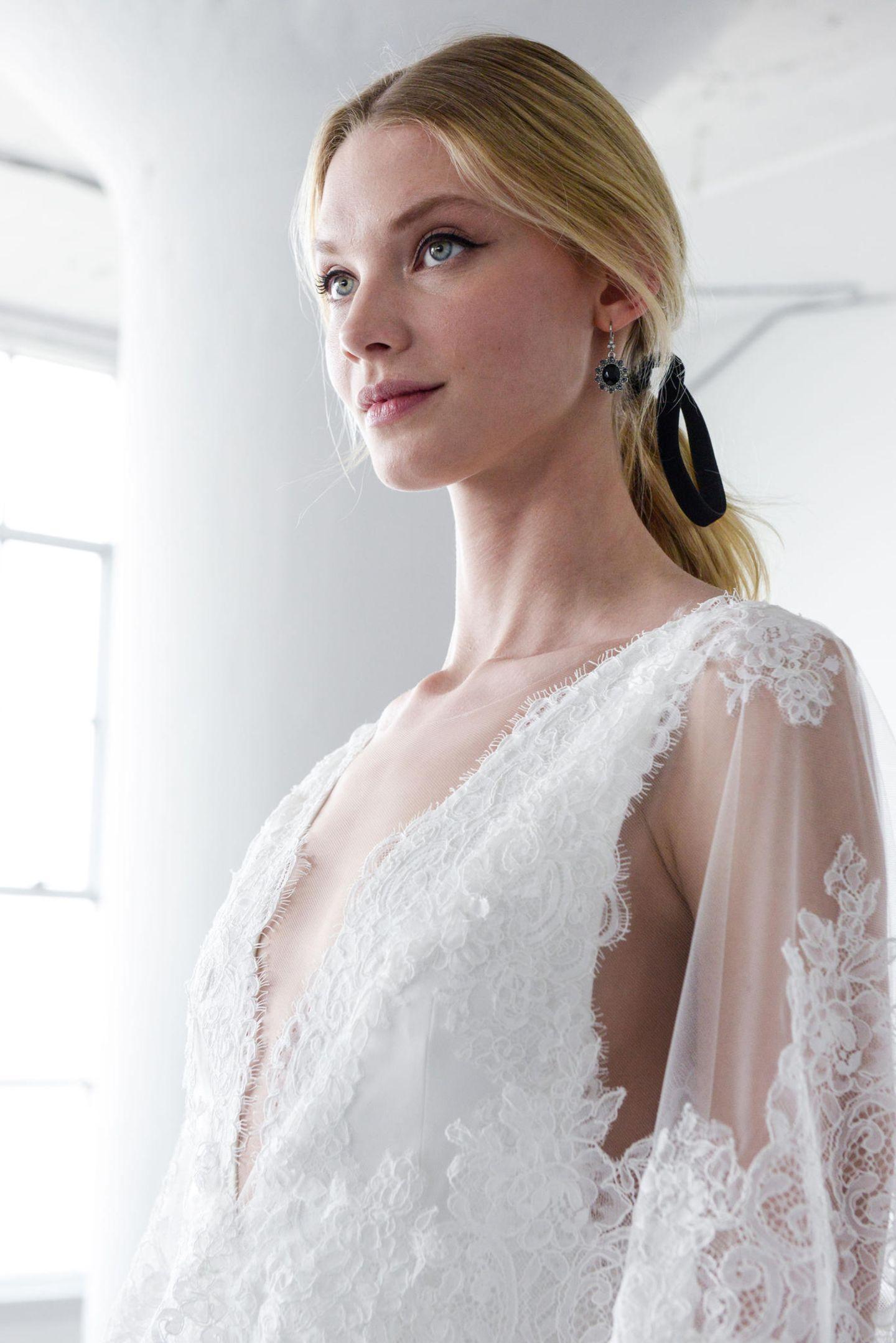 Brautfrisuren: Braut mit tiefsitzendem Zopf und Schleifenband im Haar