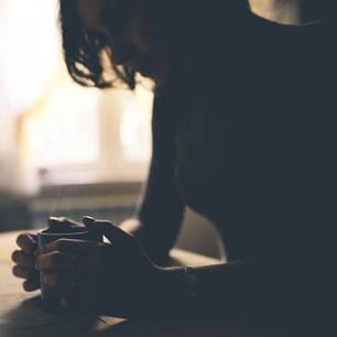 Abtreibung: Traurige Frau nachdenklich am Tisch