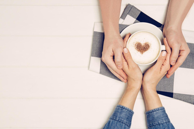 Welche Geheimnisse sollte man dem Partner erzählen? Ein Paar hält gemeinsam eine Kaffeetasse in den Händen