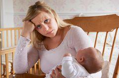 Selbstliebe: Mutter sitzt fertig im Schaukelstuhl mit Baby