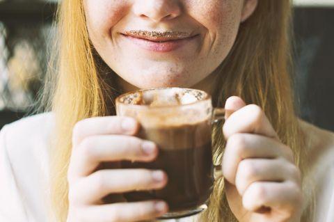 Wie werde ich möglichst schnell glücklich? Eine fröhliche Frau mit Milchschaumbart trinkt einen Kaffee