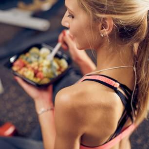 Essen nach dem Sport: Was du wirklich essen und was du vermeiden solltest: Frau in Sportkleidung hält Schale mit Essen