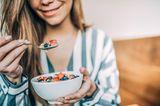 Morgenrituale der Redaktion: Eine Frau frühstückt Müsli