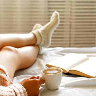 Morgenrituale der Redaktion: Eine Frau mit Notizbuch und Kaffeetasse im Bett