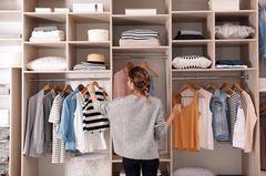 Kleiderschrank-Hacks: Frau vor einem Kleiderschrank