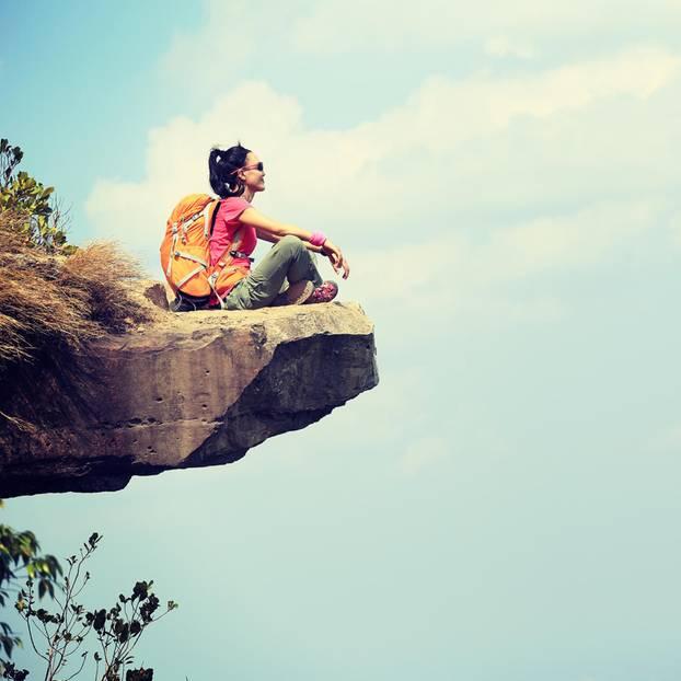 Ängste überwinden: Eine Frau sitzt auf einer Klippe
