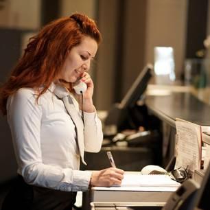 Hotelfachfrau Gehalt: Hotelfachfrau telefoniert an der Rezeption