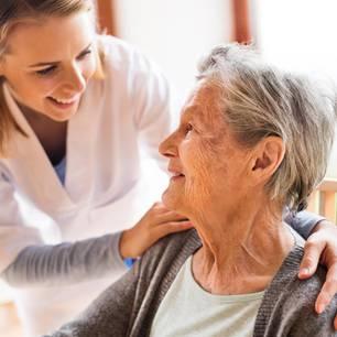 Altenpfleger Gehalt: Altenpflegerin legt Hände auf Schulter einer älteren Frau