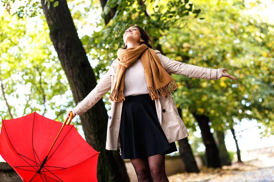 Leben genießen: Eine Frau mit Regenschirm in der Hand genießt die Luft