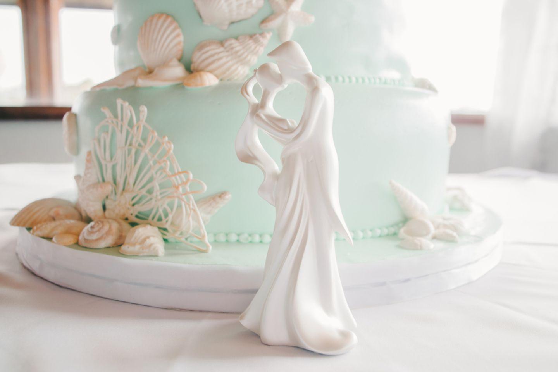 Porzellanhochzeit: Bedeutung, Bräuche und Geschenkideen: Brautpaar aus Porzellan steht vor einer Hochzeitstorte