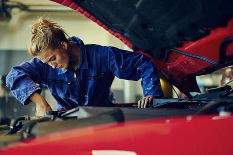 Kfz-Mechatroniker Gehalt: Frau schraubt an Auto