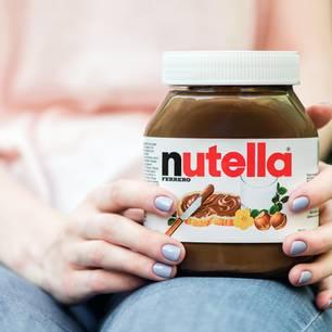 Frau hat Nutella-Glas auf dem Schoß