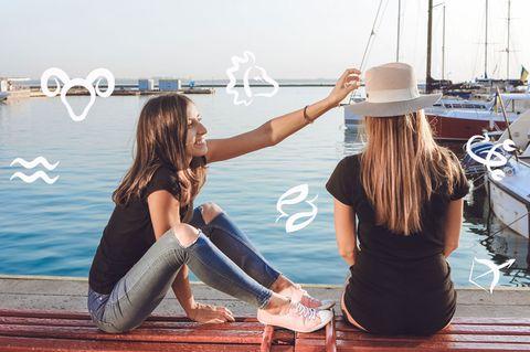 Gründe, warum jeder einen Stier im Leben braucht: Zwei Frauen sitzen am Meer, eine richtet der anderen den Hut