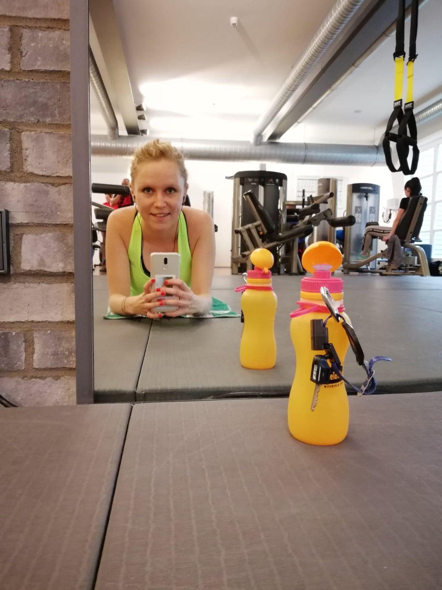 Kraftquellen der Redaktion: Eine junge Frau macht ein Spiegelselfie im Fitnessstudio